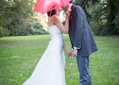 Sposi con ombrello rosso sotto la pioggia
