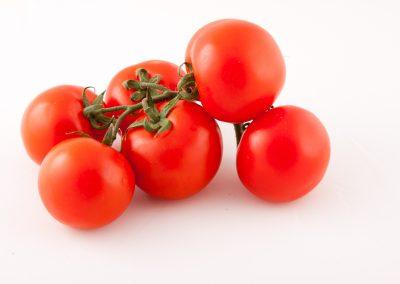 Pomodorini a grappolo rossi su fondo bianco